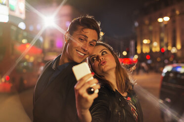 Couple taking picture together with cell phone at night - CAIF14268