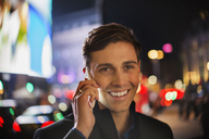 Man talking on cell phone on city street at night - CAIF14271