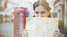 Woman holding map on city street - CAIF14274