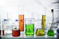 Beakers of various solutions on shelf in lab - CAIF14283