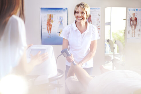 Smiling physical therapist using ultrasound probe on patient's leg - CAIF14304