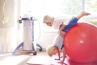 Physical therapist holding boy over large fitness ball - CAIF14310