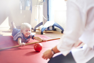 Physical therapist guiding boy rolling ball with stick - CAIF14313