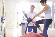 Physical therapist guiding woman on stationary bike - CAIF14319
