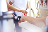 Masseuse applying gel to woman's leg in preparation for ultrasound probe - CAIF14322