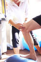 Physical therapist guiding knee of man stepping onto fitness ball - CAIF14337