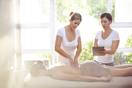 Masseuses with digital tablet massaging woman's back - CAIF14340