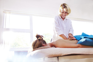 Masseuse massaging woman's back - CAIF14346
