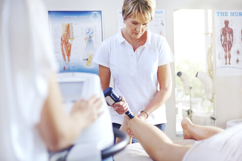 Physical therapist using ultrasound probe on woman's leg - CAIF14349