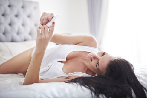 Woman laying on bed texting with cell phone - CAIF14385