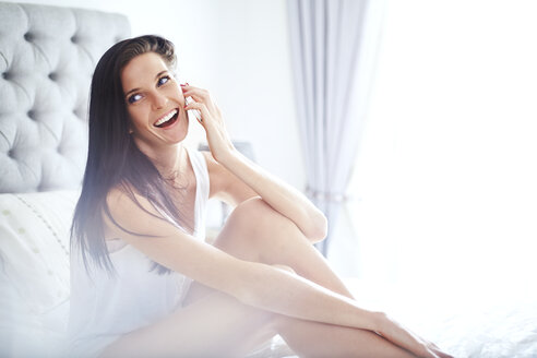 Smiling woman talking on cell phone on bed - CAIF14391