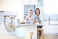 Portrait smiling women leaning on kitchen counter - CAIF14412