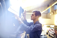 Mechanic working on car in auto repair shop - CAIF14430