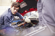 Mechanic working on car engine in auto repair shop - CAIF14436