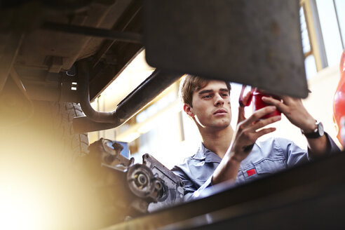Mechanic working in auto repair shop - CAIF14439
