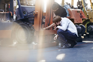 Mechanic and customer examining forklift in auto repair shop - CAIF14451