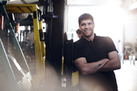 Portrait confident mechanic leaning on forklift in auto repair shop - CAIF14454