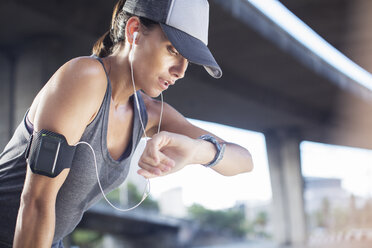 Woman looking at watch after exercising on city street - CAIF14517