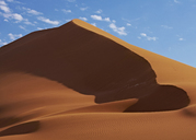 View of sand dunes in desert with blue sky and clouds in background - CAIF14535