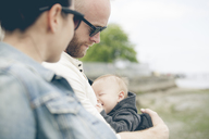 Parents wearing sunglasses holding little baby outdoors - CAIF14553