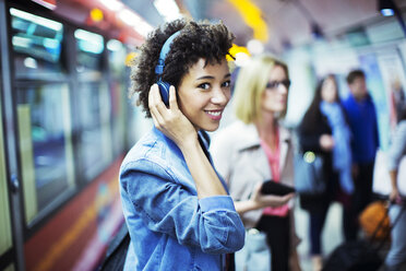 Smiling woman listening to headphones in subway - CAIF14556