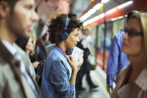 Woman listening to headphones in train station - CAIF14559