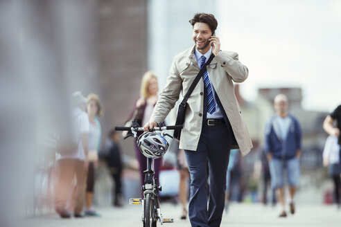 Businessman talking on cell phone pushing bicycle in city - CAIF14562