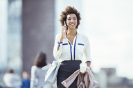 Businesswoman talking on cell phone in city - CAIF14574