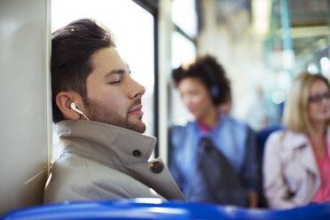 Businessman napping and listening to earbuds on train - CAIF14577