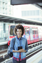 Woman holding digital tablet in train station - CAIF14580