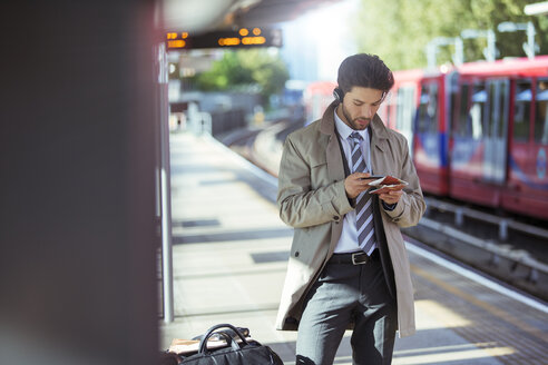 Businessman using cell phone in train station - CAIF14583