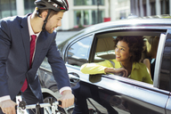 Businessman on bicycle talking to woman in car - CAIF14586