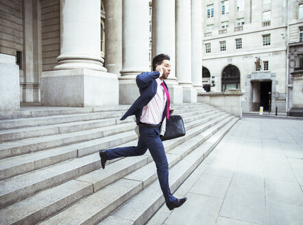 Businessman on cell phone running on city staircase - CAIF14589