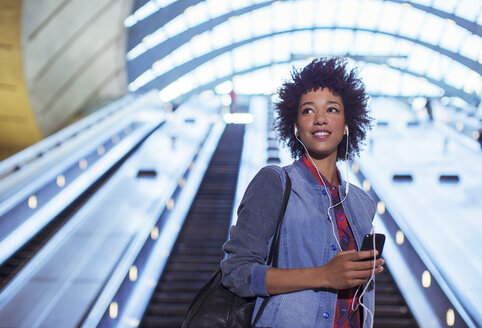 Woman listening to earbuds on escalator - CAIF14601