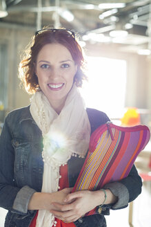 Portrait of smiling casual businesswoman holding laptop case - CAIF14640
