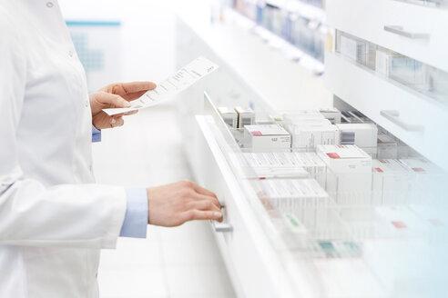 Pharmacist filling prescription in pharmacy - CAIF14685