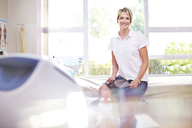 Portrait smiling physical therapist in examination room - CAIF14748