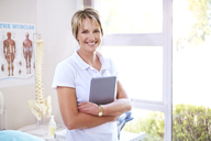 Portrait confident physical therapist with digital tablet in examination room - CAIF14754