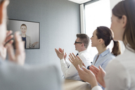 Business people clapping for businesswoman on video conference screen - CAIF14757