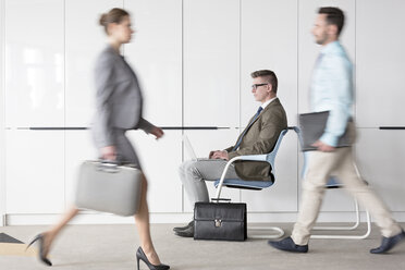 Businessman working at laptop in lobby behind business people on the move - CAIF14760