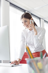 Businesswoman talking on cell phone working at computer in office - CAIF14763