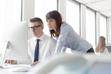Focused businessman and businesswoman working at computer in office - CAIF14769