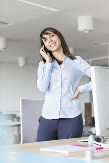 Brunette businesswoman talking on cell phone at desk in office - CAIF14778
