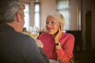 Older couple toasting each other with white wine - CAIF14802