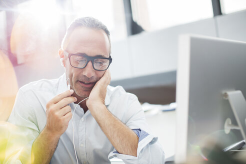 Businessman listening to earbuds at office desk - CAIF14808