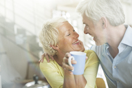 Older couple hugging with coffee cup - CAIF14811