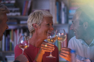 Older friends toasting each other with white wine - CAIF14814