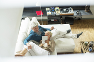 High angle view of older couple using digital tablet on sofa - CAIF14823
