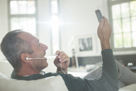 Close up of older man with earbuds talking on cell phone - CAIF14841
