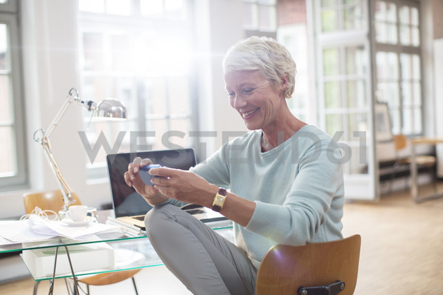 Businesswoman using cell phone at home office desk - CAIF14844